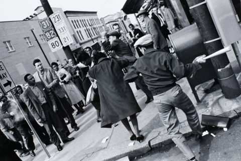 Photo by Charles Moore. Two African American women being attacked. Note the bat in the man's hand while another man pummels a woman with his fists.