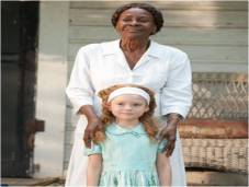 Cicely Tyson as Constantine in film version of The Help, coddling a young Skeeter