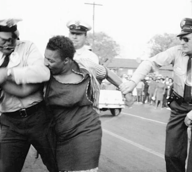 Scenes from the 1960s, police and African American woman protester